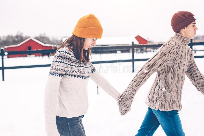 Teenage models in sweaters on snow in winter day stock photo