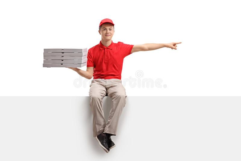 Teenage pizza delivery boy sitting on a panel and pointing stock image