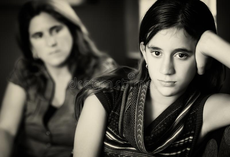 Defiant teenage girl and her worried mother. Teenage problems - Defiant teenage girl after a fight with her worried mother looking at her royalty free stock photos