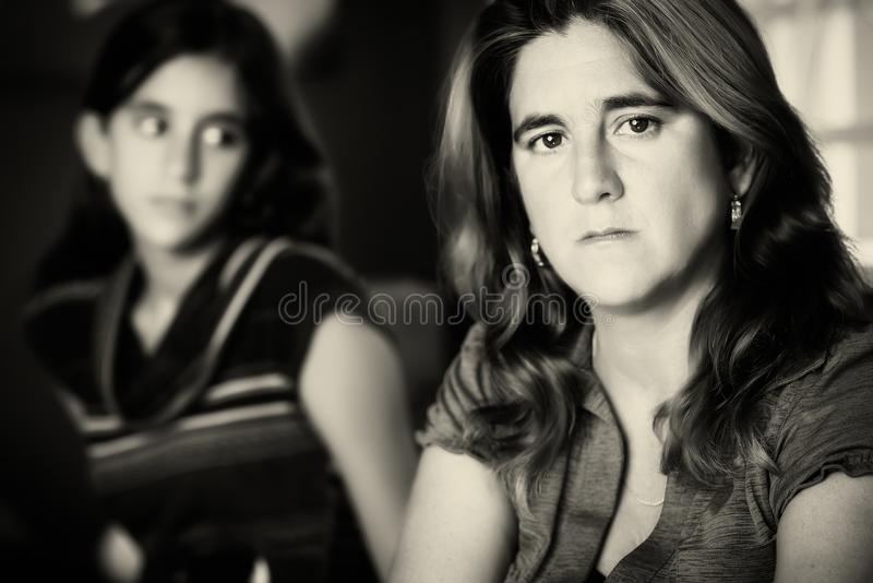 Sad and worried mother and her teenage daughter. Teenage problems - Sad and worried mother with her rebellious teenage daughter on the background royalty free stock photo
