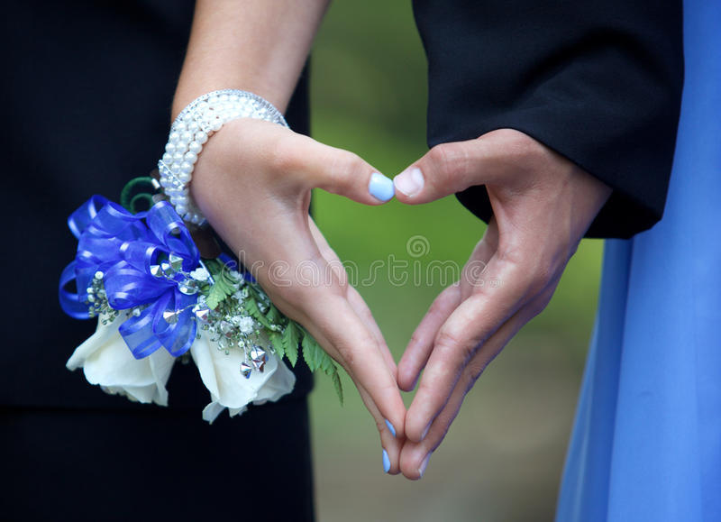 Teenage Prom Couple Forming Hand Heart Between Them. A playful teenage couple taking a prom photo. They are forming a heart out of her hands between them royalty free stock photos