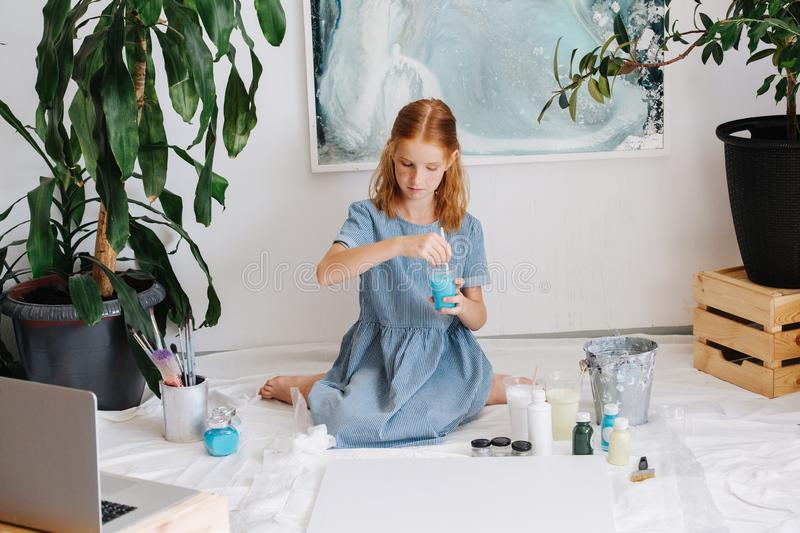 Teenage redhead girl is painting with brush on big canvas on floor in a workshop royalty free stock images