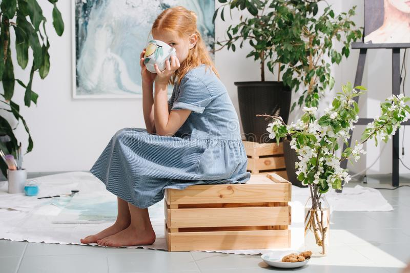 Teenage redhead girl is sitting on a box, drinking tea in a workshop stock image