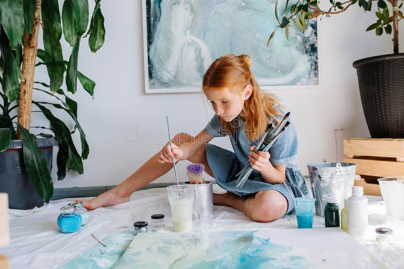 Teenage redhead girl is painting with brush on big canvas on floor in a workshop stock photo