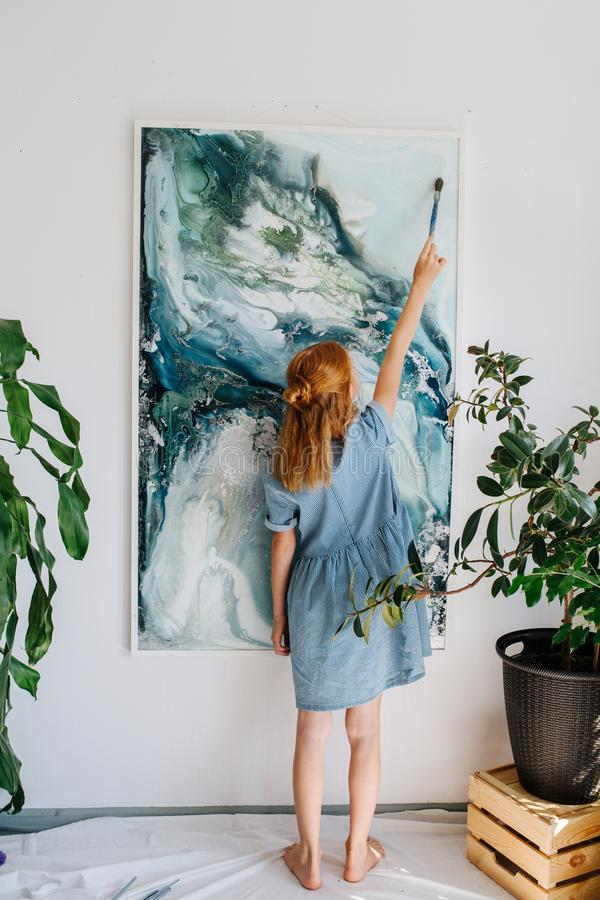 Teenage redhead girl is painting on a canvas hanging on the wall royalty free stock photo