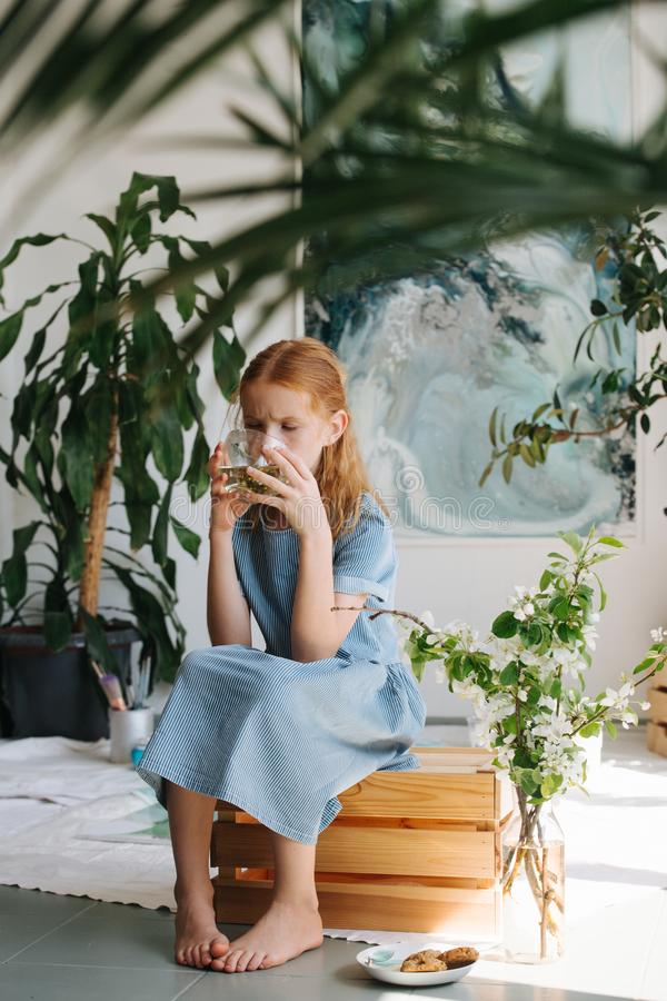 Teenage redhead girl is sitting on a box, drinking tea in a workshop royalty free stock photo
