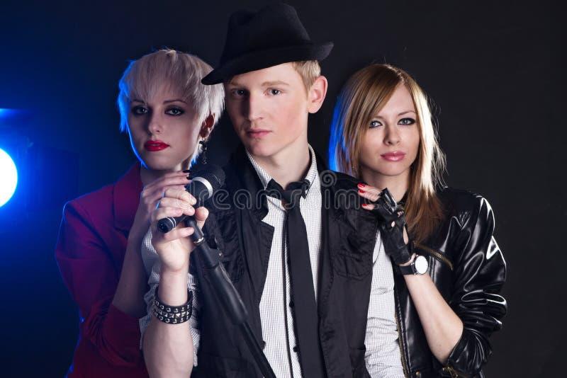 Teenage rock band. Against black background stock photography