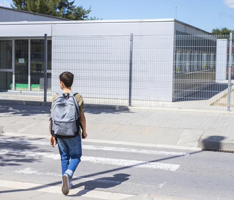 Teenage school boy with a backpack on his back walking to school stock photo