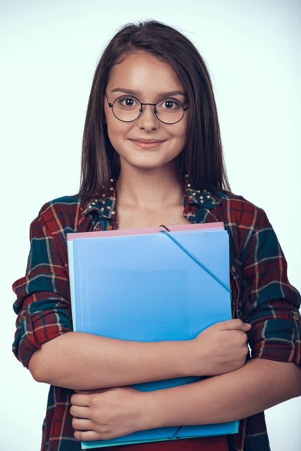 Teenage Schoolgirl in Eyeglasses Holds Books. royalty free stock photography