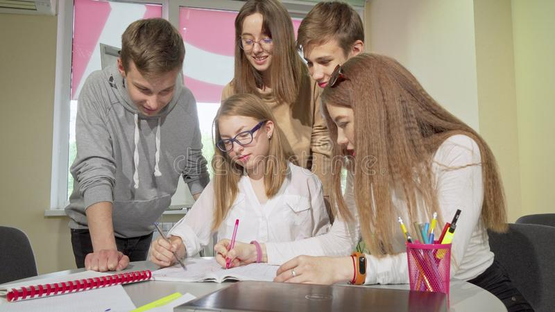 Teenage schoolkids preparing for exams together, working on laptop royalty free stock photography