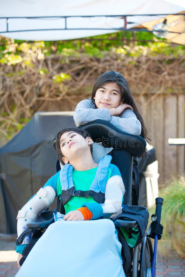 Teenage sister taking care of disabled brother in wheelchair out royalty free stock image