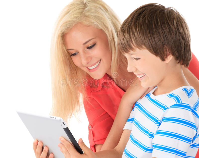 Teenage sister with young brother. Young brother showing his blond teenage sister a Kindle ( or Kobo ) e-book reader on a white background royalty free stock photography