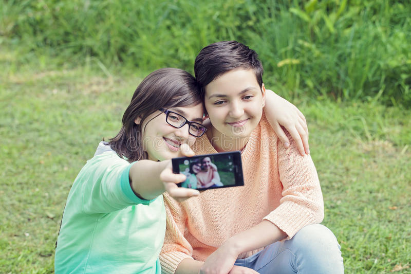 Teenage sisters with the phone stock photo