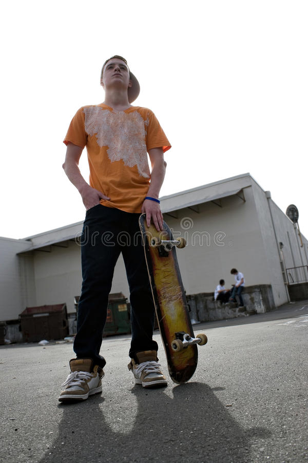 Teenage Skateboarder. A young teenage skateboarding standing with his skateboard and other kids hanging out in the background stock images