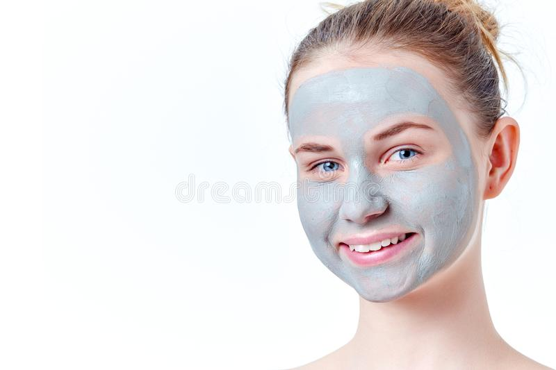 Teenage skincare concept. Smiling young redhead girl with dried clay facial mask portrait, isolated on white background. stock photography