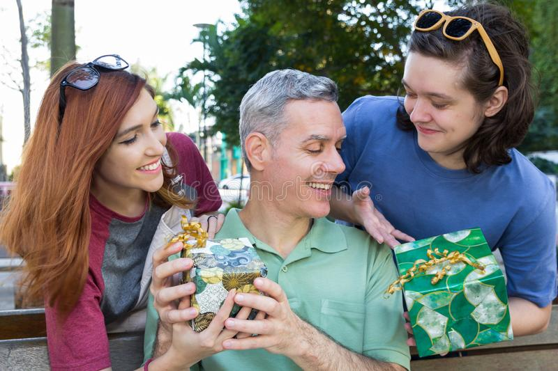 Teenage son and daughter are giving a present to dad. Father Day stock photo