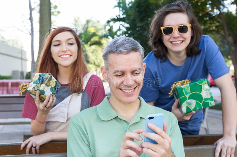 Teenage son and daughter surprise dad by giving a present. Fathers Day. Concept of family, holiday stock photos