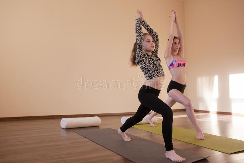 Teenage sport. Yoga for kids. Zen life, stretching exercises for girls in studio. Gym background with free space, healthy lifestyle, asana concept stock photography