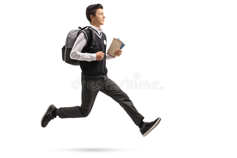 Teenage student with a backpack and books in mid-air. Full length profile shot of a teenage student with a backpack and books in mid-air isolated on white royalty free stock photo