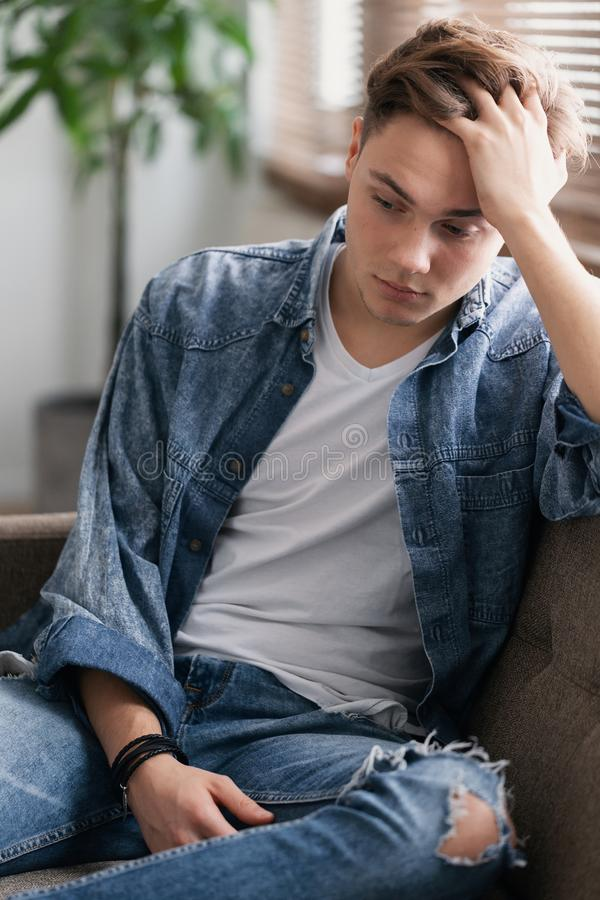 Teenage student sitting alone at home waiting for his father stock photography