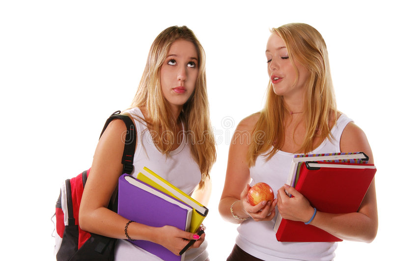 Teenage students. Half body portrait of two blond teenage high school students with backpack, books and apple, isolated on white background stock images