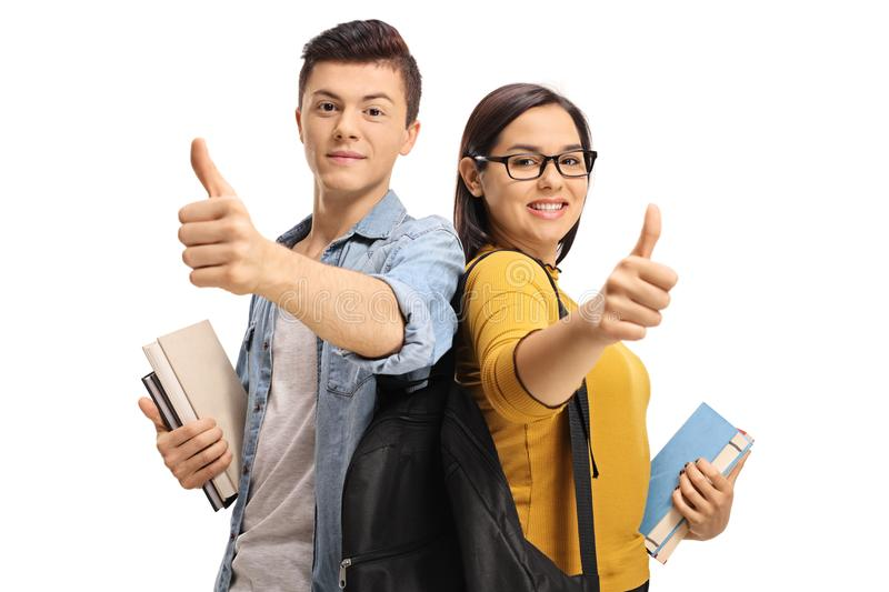 Teenage students with backpacks and books making thumb up gestures royalty free stock photography