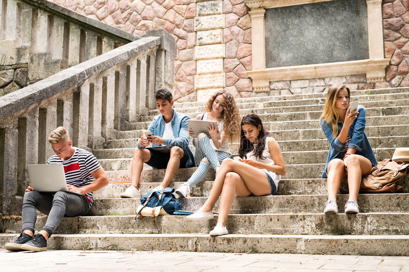 Teenage students with gadgets outside on stone steps. stock photography