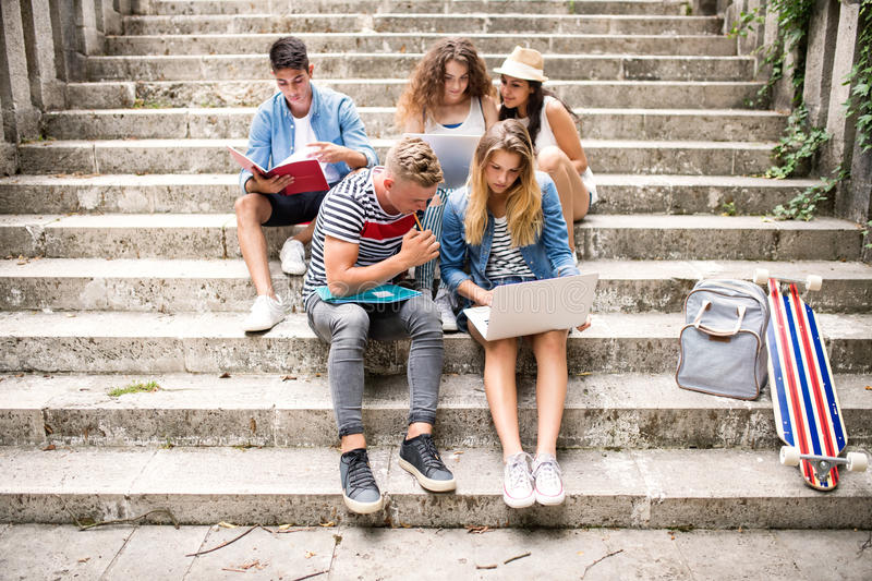 Teenage students with laptop outside on stone steps. stock photo