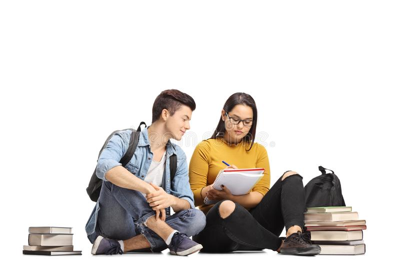 Teenage students seated on the floor studying together. Isolated on white background stock photos
