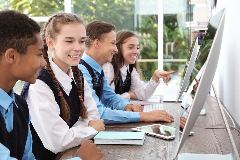 Teenage students in stylish school uniform. At desks with computers royalty free stock photography