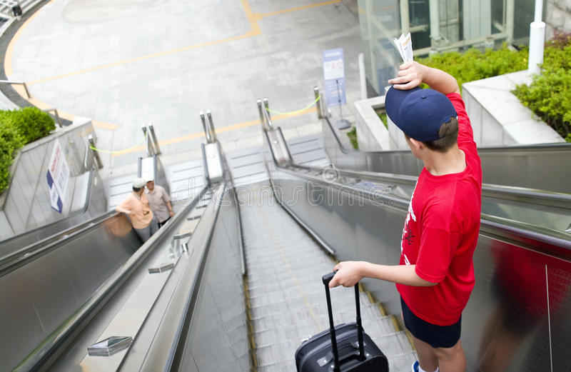 Teenage tourist. A teenage boy with a suitcase on escalator royalty free stock photos
