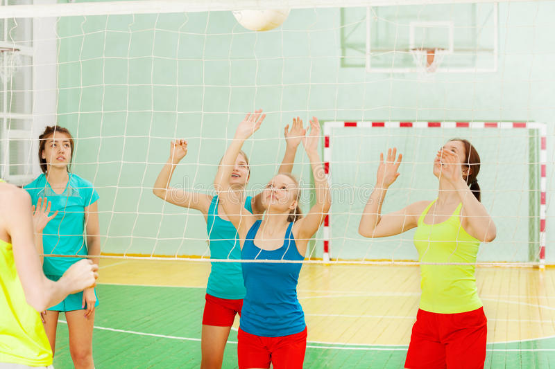 Teenage volleyball team receiving the ball stock photo
