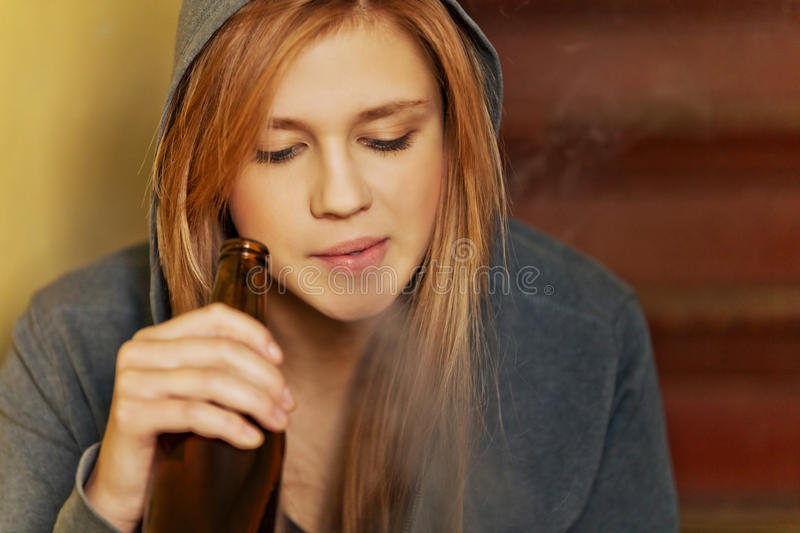 Teenage woman drinking beer and smoking cigarette.  royalty free stock photos