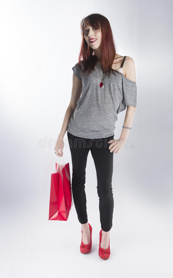 Teenage Woman Holding Single Red Shopping Bag stock photography