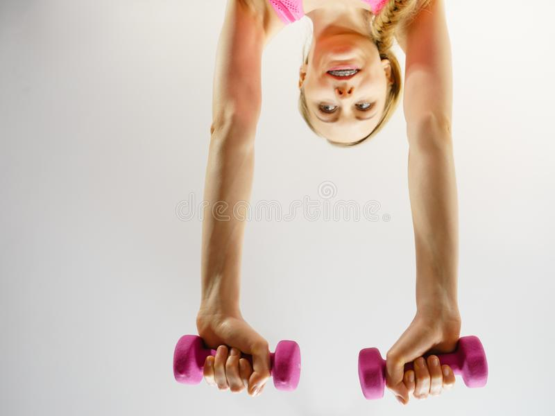 Teenage woman working out at home with dumbbell. Teenage young woman working out at home with small light dumbbells. Training at home, being fit and healthy stock photo