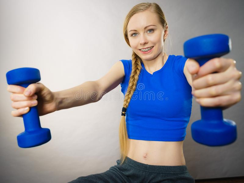 Teenage woman working out at home with dumbbell. Teenage young woman working out at home with small light dumbbells. Training at home, being fit and healthy royalty free stock photo