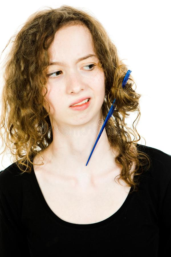 Teenaged blond girl with hair having tangled hair dressing problem - jammed comb royalty free stock images