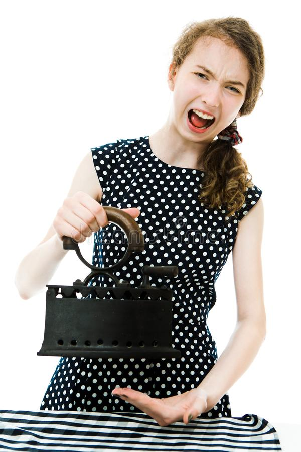 Teenaged girl in dot`s dress try temperature before using old antique iron - pain stock images