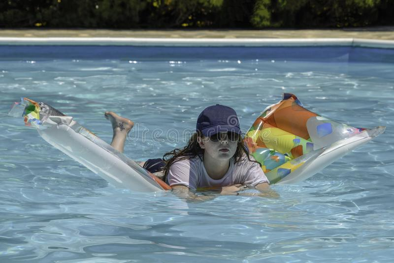 Teenage girl floating on an airbed royalty free stock photos