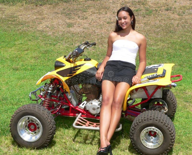 Teenaged girl leaning on yellow ATV stock photography