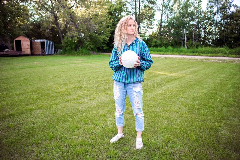 Teenaged girl outdoors with a volleyball stock photo