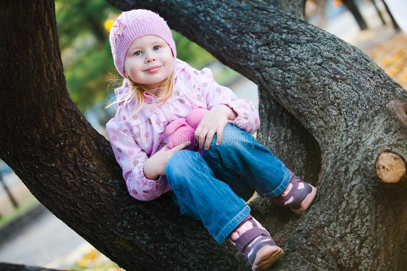 Teenaged girl sitting with teddy bear on tree - purple dots jacket. royalty free stock images