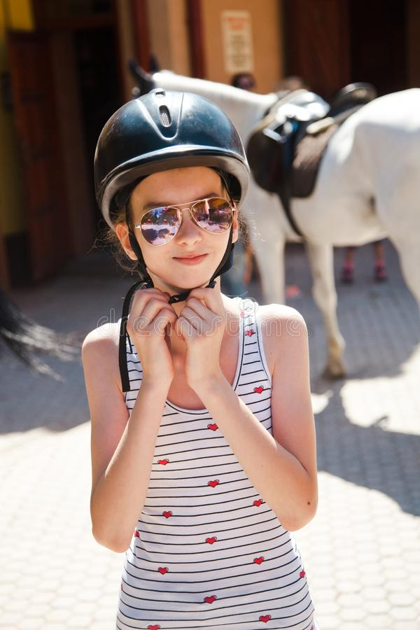 Teenaged girl wearing her helmet before training royalty free stock image