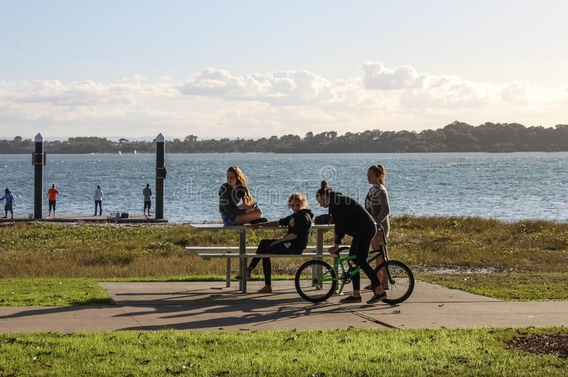 Teenaged girls at a picnic table out by the water on a late Saturday afternoon in the Redlands Queensland Australia May 23 2015 royalty free stock photos