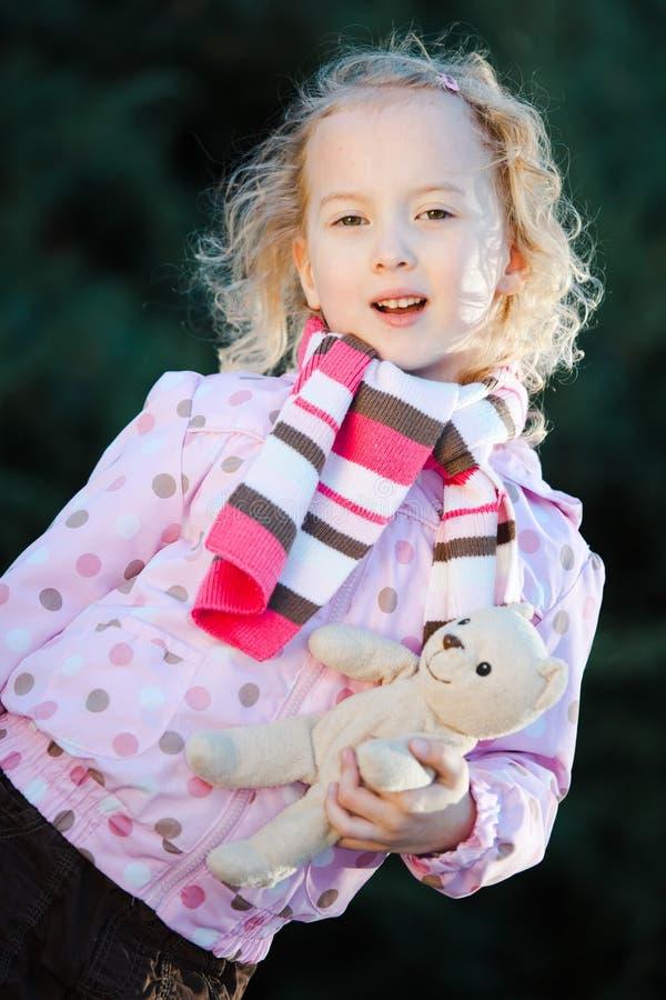 Teenaged Mädchen, das mit purpurroter Jacke der zeit- Punkte des Teddybärbärn-Herbstes aufwirft stockbild