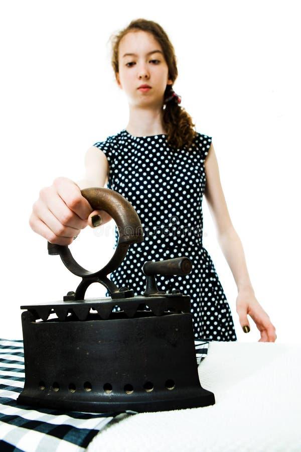 Teenaged Mädchen im Kleid des Punktes unter Verwendung des alten antiken Eisens - Weinlese Co lizenzfreies stockfoto