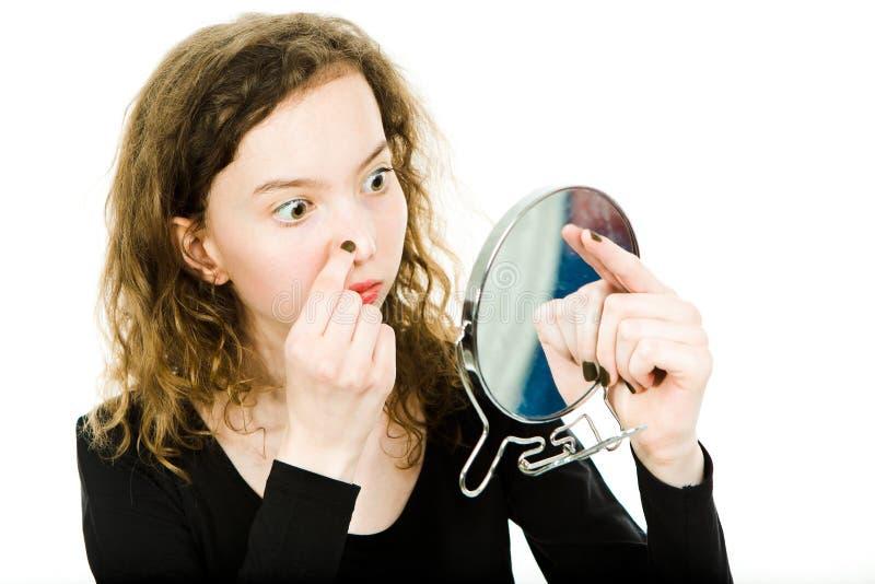 Teenagedmeisje die huid in spiegel controleren - neus royalty-vrije stock afbeeldingen