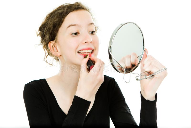 Teenagedmeisje die in zwarte kleding omhoog in spiegel maken maken - lippenstift royalty-vrije stock foto