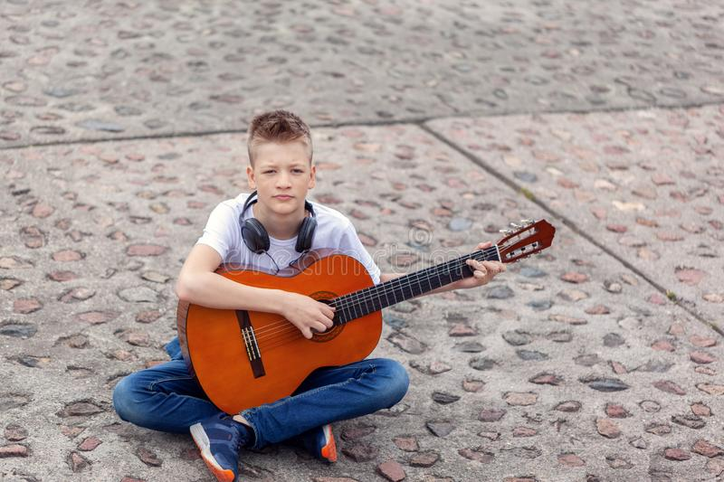 Teenager with acoustic guitar and headphones sitting in the park stock images
