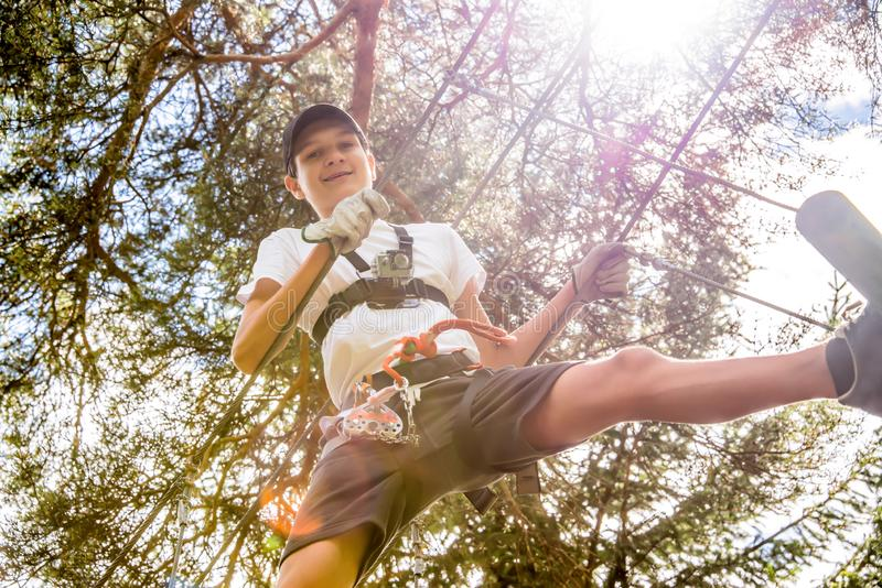 Teenager with action camera having fun on high ropes course, adventure park, climbing trees in forest royalty free stock photo